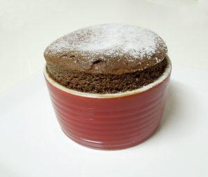 A chocolate souffle in a red ramekin, the dessert from this list of Valentine's Day recip