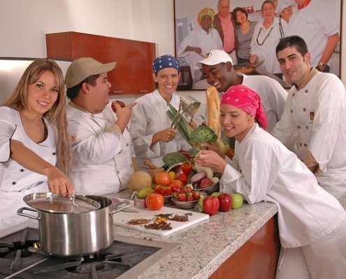 Young chefs learning the fundamentals of cooking in a group wearing chefs whites in a commercial kitchen