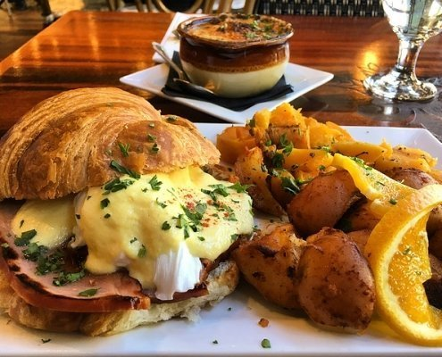 Croissant egg sandwich with tots and an orange wedge for garnish, soup in a brown crock in the background