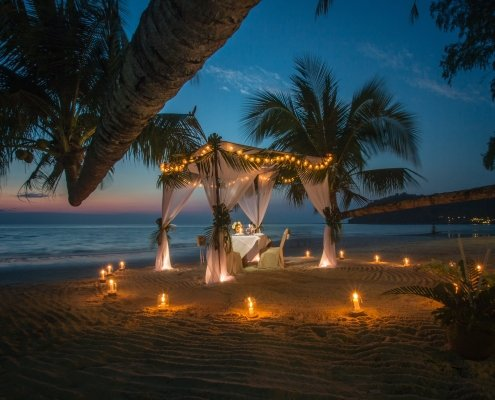 A romantic table set in a pergola on a beach