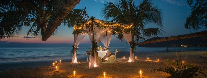 A romantic table set in a pergola on a beach