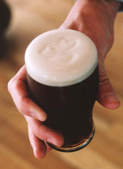 Hand holding half pint of Guinness Beer