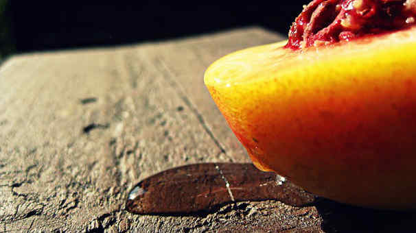aphrodisiac peach sliced in half on a wooden background