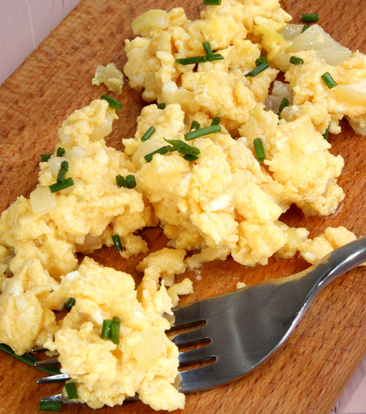scrambled duck eggs with fine herbs on a wooden board
