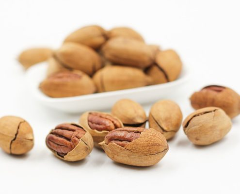 white bowl with nuts and several laying in front
