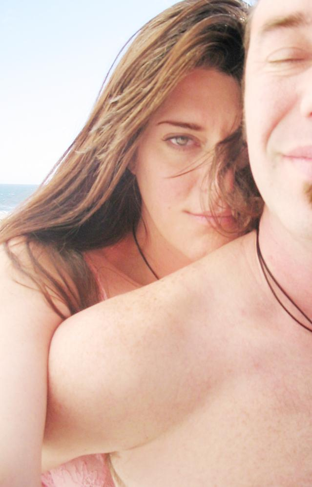 a closeup of a woman's face and arm reaching over a man's naked shoulder with the side of his face exposed