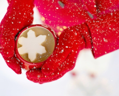 woman in red gloves holding a hot chocolate cocktail with a snowflake marshmallow
