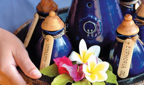 Two hands carrying a tray of blue clay bottles for an ayurvedic treatment