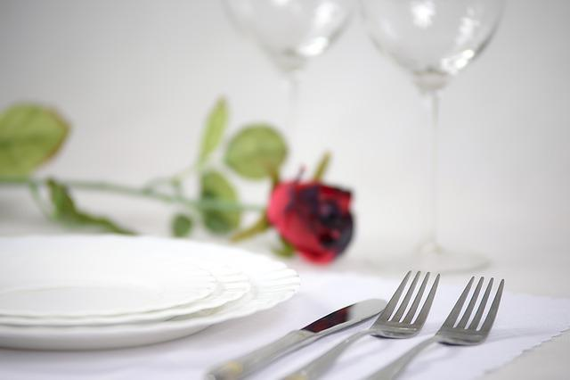 closeup of dinner table setting with a red rose to illustrate what we consider romantic