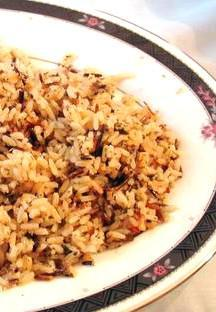 closeup of brown rice pilaf in a white bowl with black trim