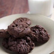 Cloesup of chocolate chocolate chip cookies on a white plate with a tall glass of milk