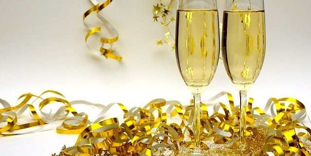 Saffron Fleurtation Champagne cocktails in 2 glasses with gold confetti