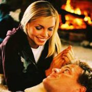 man and woman laying on a white rug in front of a roaring fire