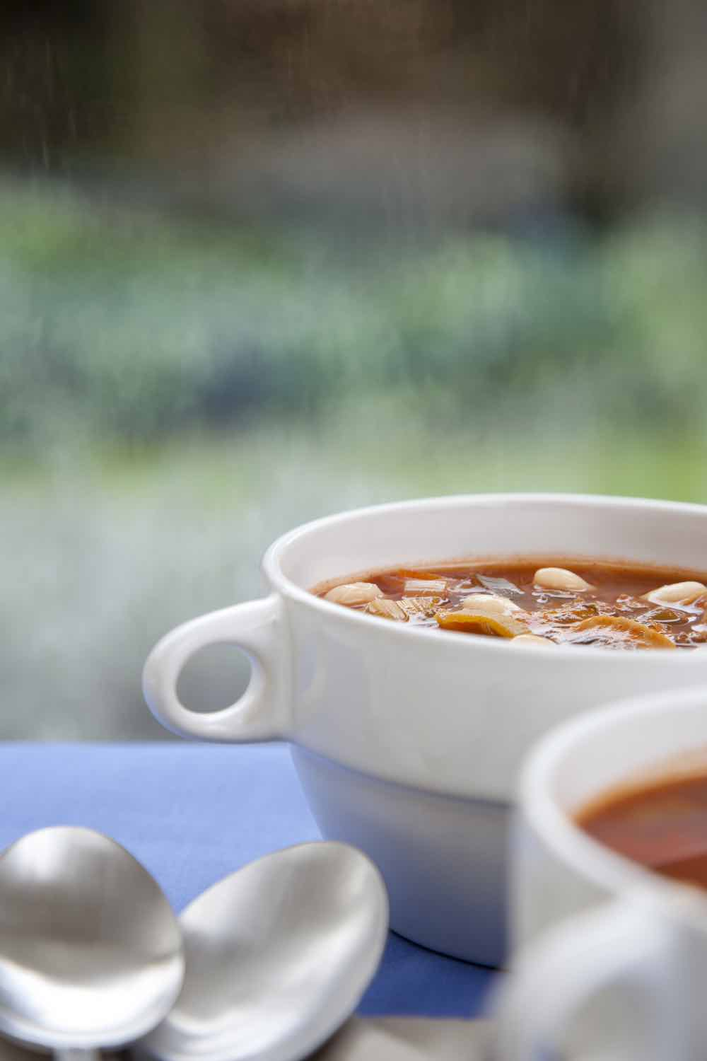 WhiteVegetarian White Bean Chili with Chocolate in a white bowl on a blue tablecloth