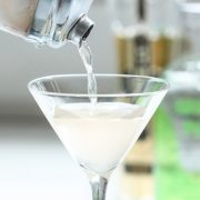 Yazi Mischief - a spicy vodka drink being poured from a shaker into a martini glass
