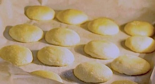 closeup of peanut butter and jelly cookies on a baking sheet covered with white parchment in the oven