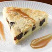 Closeup of Black Mission Fig Clafoutis on white plate with two streaks of caramel sauce