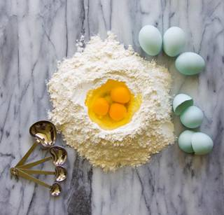 Blue heirloom eggs in flour with measuring spoons