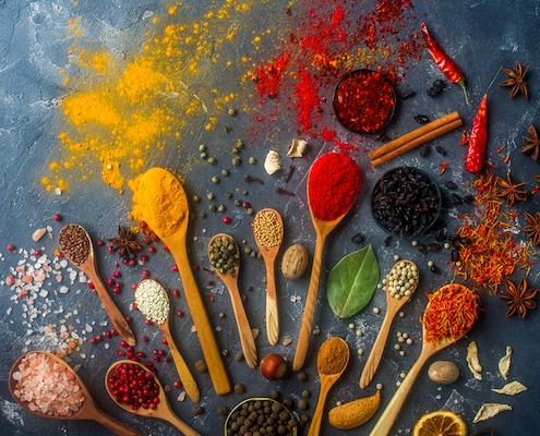 a rainbow of spices on cooking spoons to illustrate cook with spices