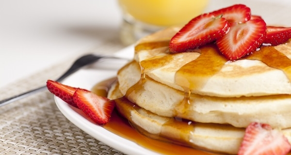 stack of three buttermilk pancakes on a plate with strawberry slices and maple syrup. Partial glass of orange juice in background.