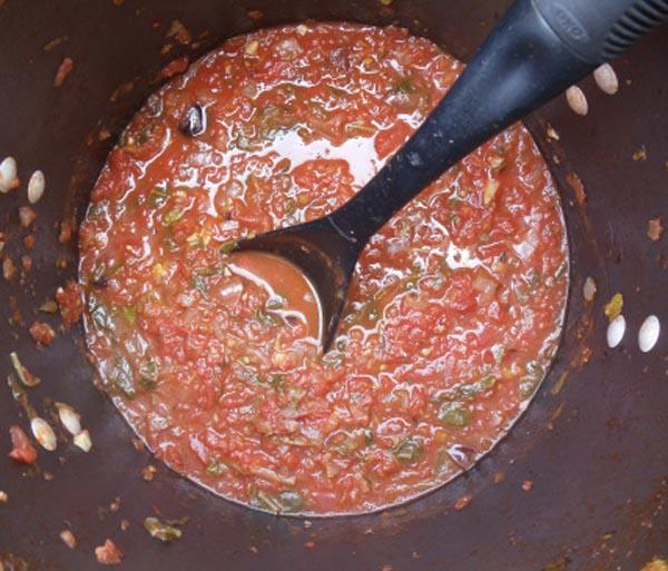 Puttanesca sauce in a pot with a black spoon