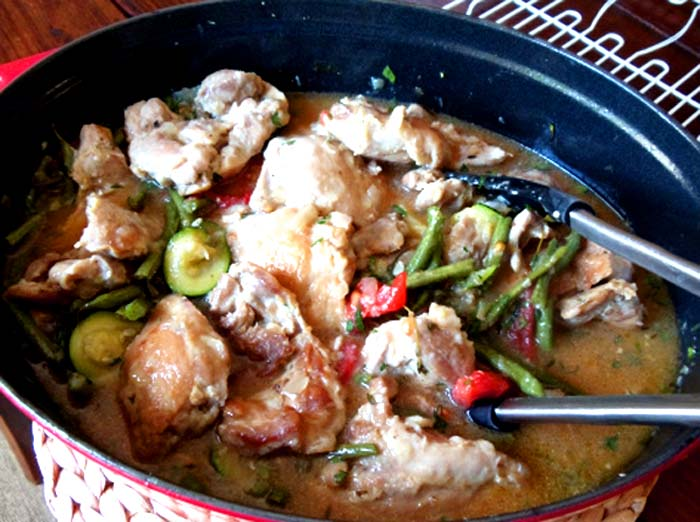 braised chicken with lemon and summer vegetables in an enamel pot with silver and black tongs