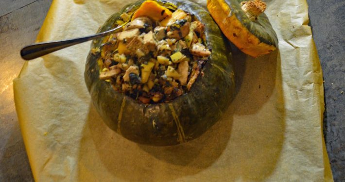 Vegetarian Roasted, Stuffed Kabocha Squash on top of parchment with a large, silver serving spoon