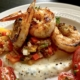 closeup of healthy shrimp recipe on top of bulgar salad and yogurt sauce on a white plate with picked grape tomatoes