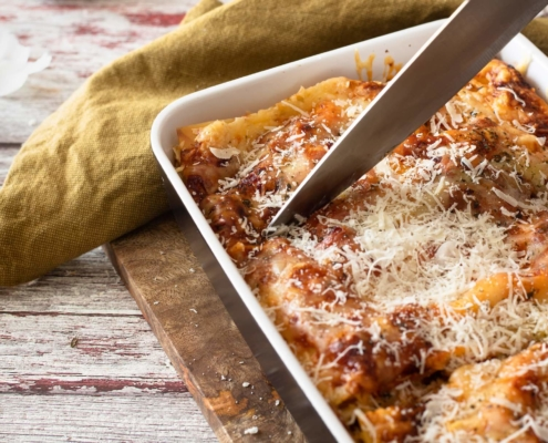 closeup of meatless lasagna in a baking dish with someone cutting it with a chef's knife