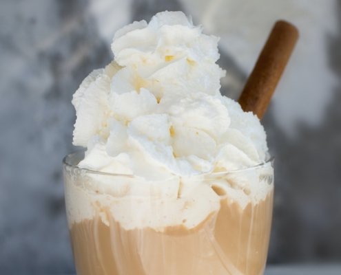 coffee cocktail topped with whipped cream and a cinnamon stick