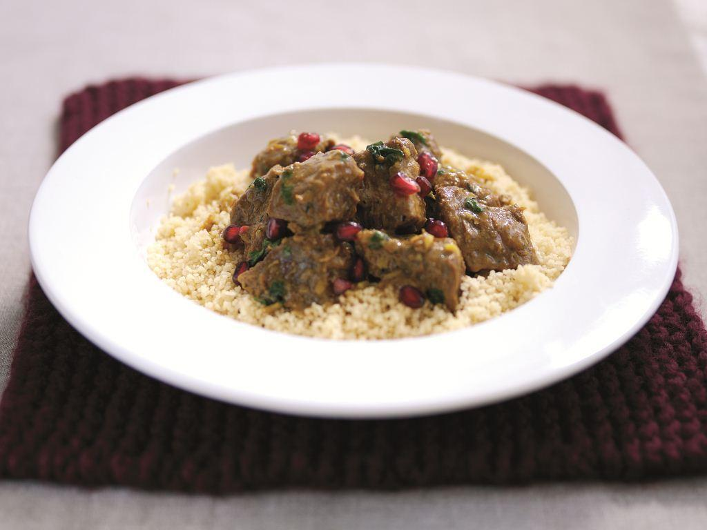 Lamb Tagine with Pomegranates over Couscous in a White Bowl