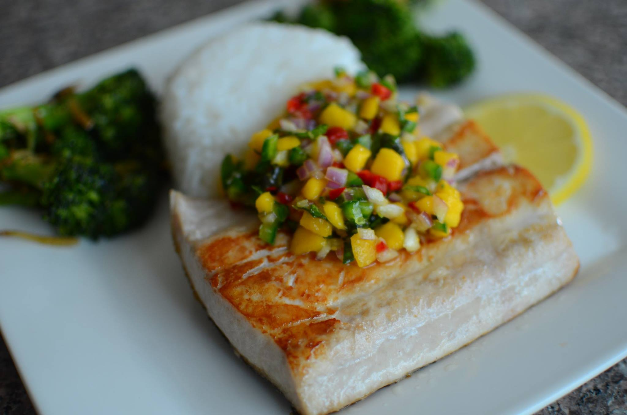 Closeup of seared mahi-mahi with fresh mango salsa and rice in the background on a white plate