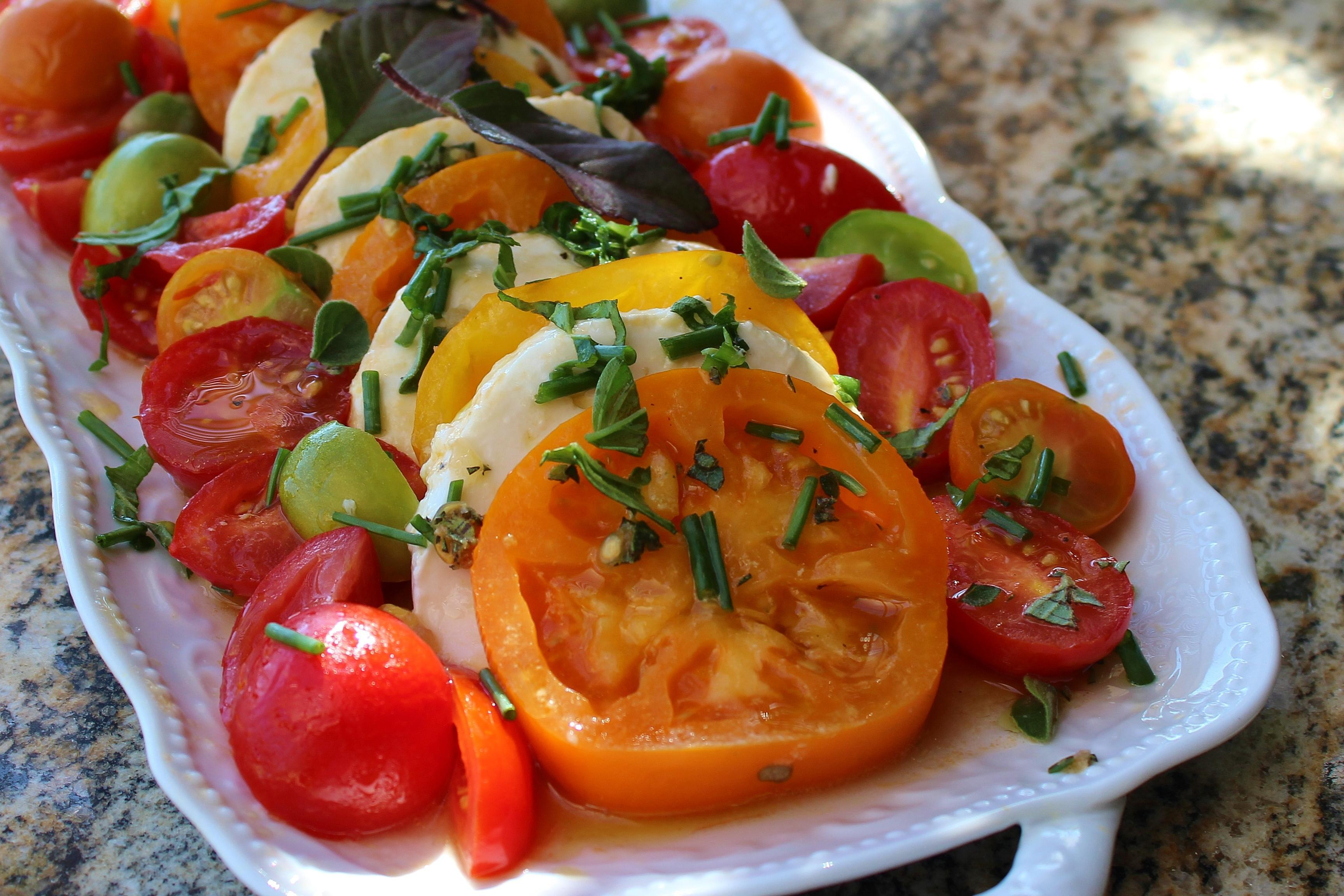 closeup of tomato mozzarella salad on a white serving platter
