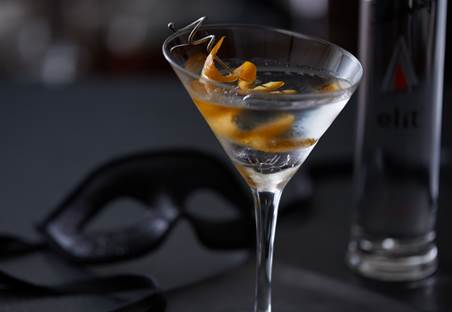 closeup fo Smoke on the Water, the sexy vodka cocktail in a martini glass with an orange twist. A black mask is in the background