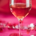 Pink wine on a pink background with valentine confetti to illustrate best valentine wine