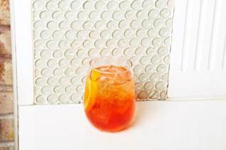 An Aperol Spritz in a rocks glass against a white background