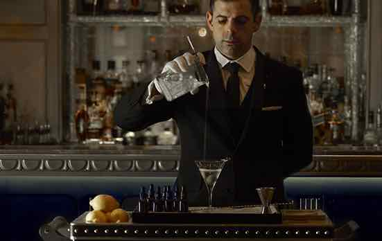 Man holding a martini glass at the Martini Trolley in The Comnaught, knows as the world's best cocktail bar