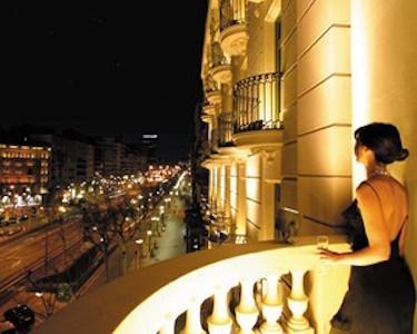 Woman in black dress standing on balcony of the Majestic