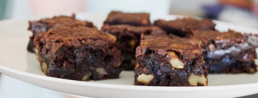 gluten-free chocolate chunk brownies on a white plate being held by a woman's hand