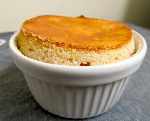 Closeup of Annette's lemon soufflé in a while ramekin on a gray background