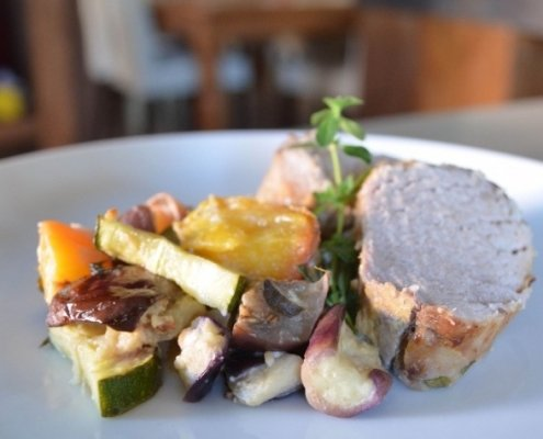 Closeup of Pork Loin with Peach Ratatouille on a blue plate