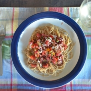 whole wheat spaghetti with raw tomato sauce on a plaid placemat with a glass of white wine