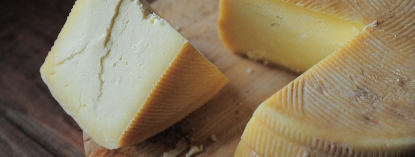 closeup of wheel of cheese with slice taken out and sitting beside it on a cutting board