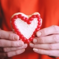 misshapen heart sugar cookie in a man's hands to illustrate the meaning behind valentine's day