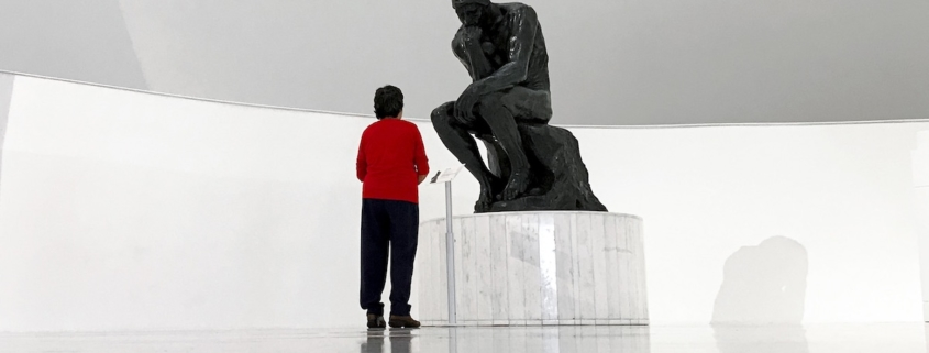 image of man in red shirt standing in front of The Thinker to illustrate that thinking burns calories