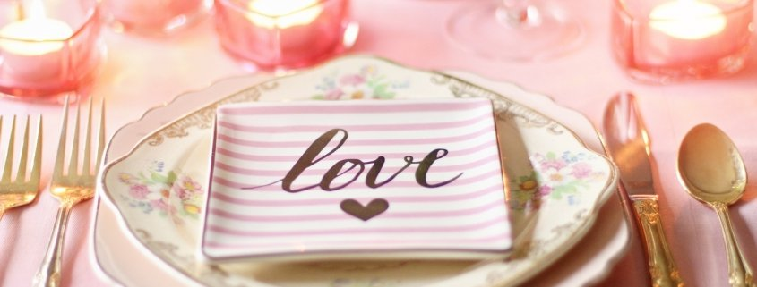 Table setting for Valentine's Day with a love napkin and pink candles