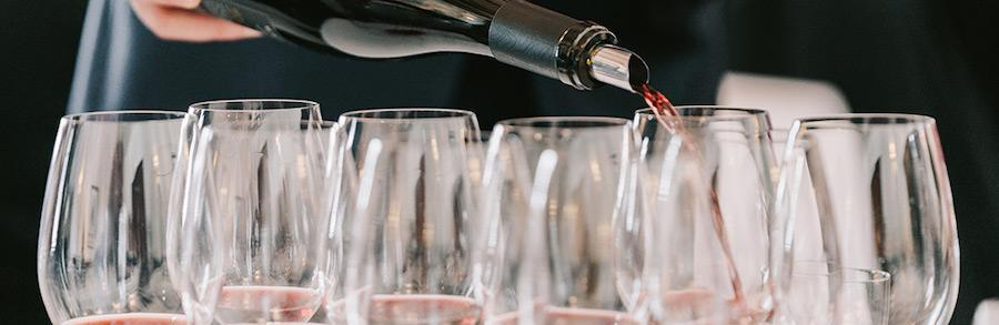 Sommelier pouring wine into multiple glasses at World of Pinot Noir event
