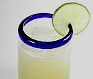 Closeup of Vanilla Margarita in glass with blue rim and lime wedge
