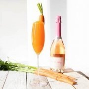 Easter Cocktail in a champagne flute with a bottle of sparkling wine behind it and carrots laying on the table