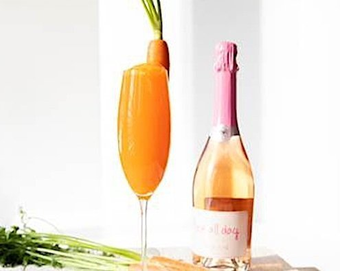Closeup of Easter Cocktail in Champagne flute with bottle of sparking wine behind it on white background